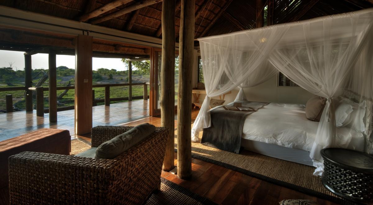 Honeymoon-Suite in einem Partnerhotel von afrika tours individuell mit Himmelbett und Balkonaussicht auf ein Wasserloch mit Wildlife