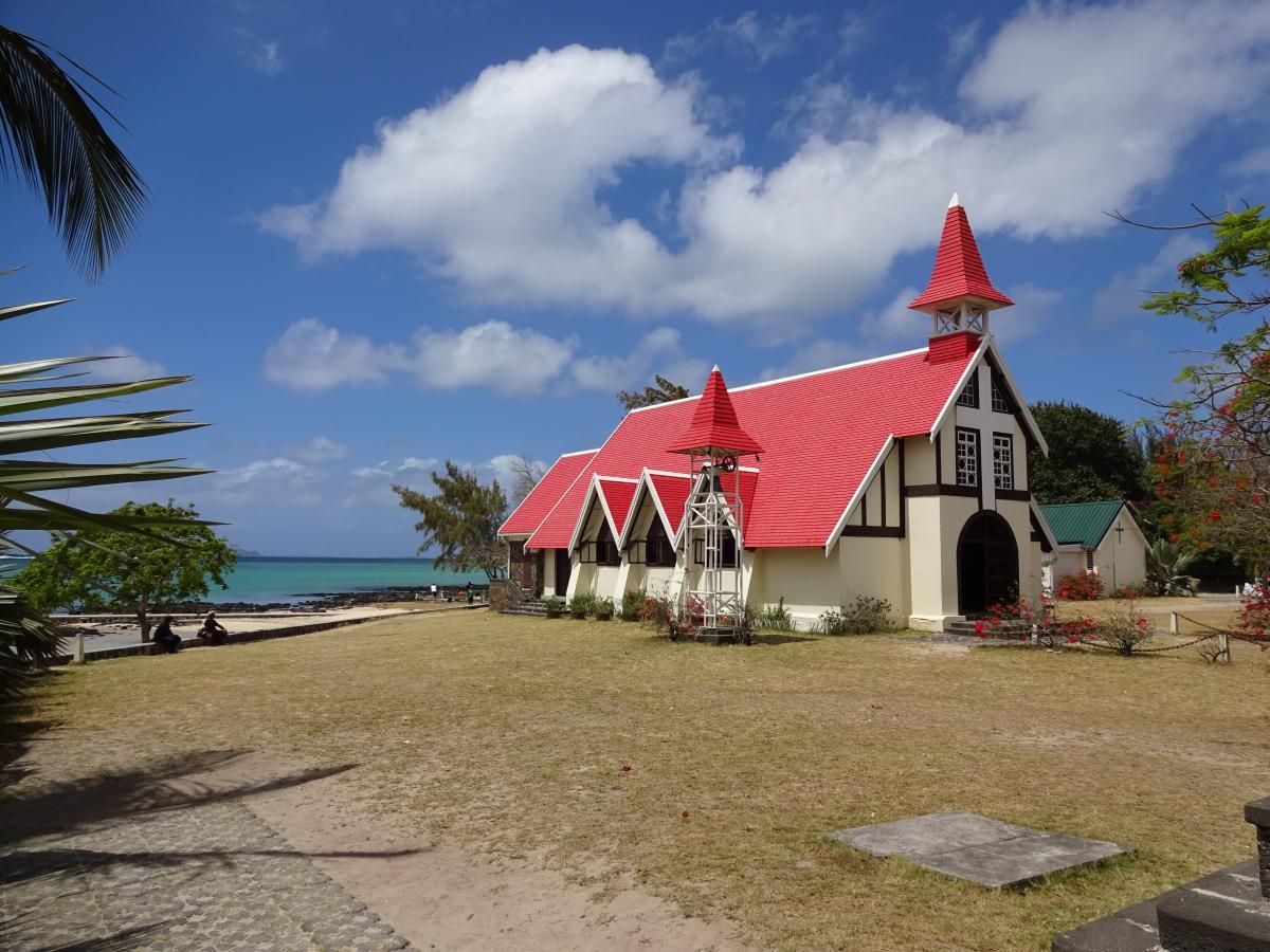 weiße Kirche mit Rotem Dach zwischen Palmen am Strand von Mosambik mit Meer im Hintergrund und weißen Wolken am Blauen Himmel