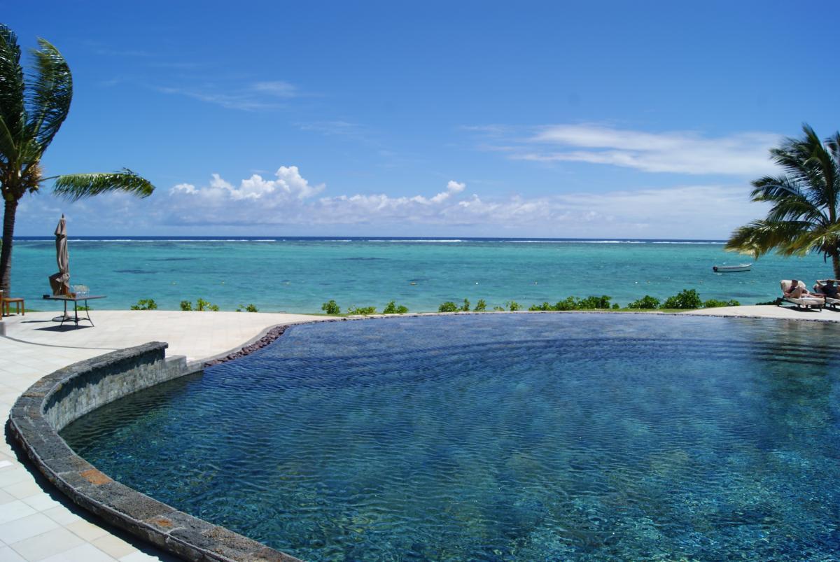 Infinity Pool mit Blick aufs Meer am Strand von Mosambik bei strahlend blauem Himmel und Sonnenschein, Palmen stehen an den Seiten des Pools