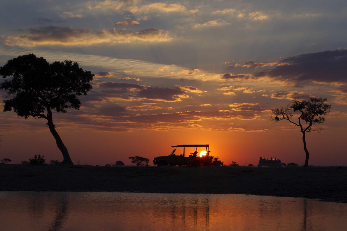 Namibi mit einem Sonnenuntergang und den Umrissen von einem Safari Jeep und einem Tisch mit Candlelight Dinner im Sonnenuntergang in seinen glühenden Farben