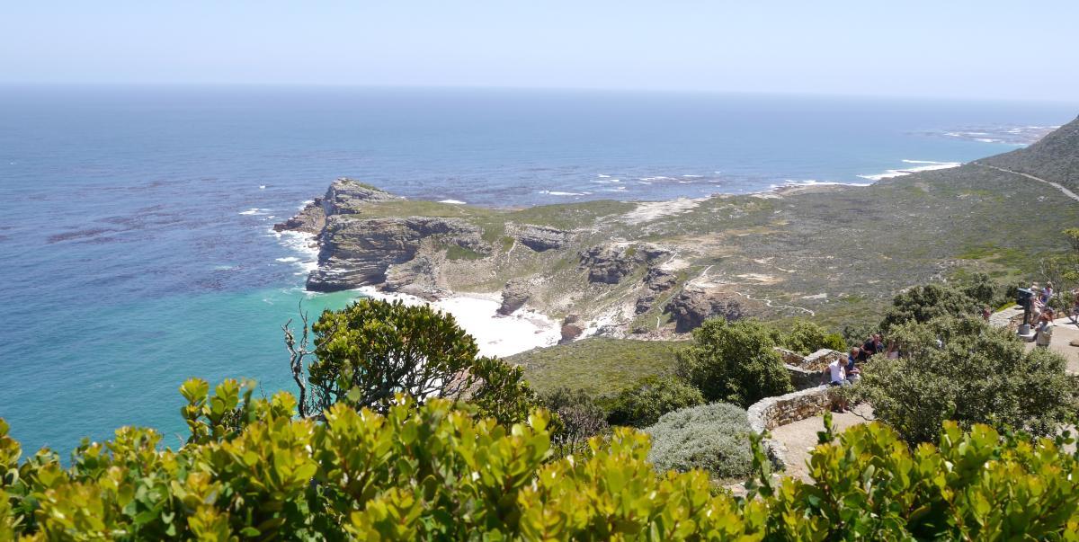 Panoramaaussicht auf das Kap der guten Hoffnung bei Kapstadt. Hier treffen zwei Weltmeere aufeinander, der Indische Ozean und der Atlantik. Die Sonne scheiint auf die felsigen Klippen und das Meer strahlt türkisblau.