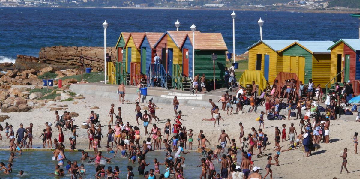 die bunten Häuschen dienen am Strand von Kapstadt als Umkleiden und sind als Fotomotiv sehr beliebt. Davor baden Einheimische und Touristen am weißen Sandstrand im blauen Meer. Die Sonne scheint