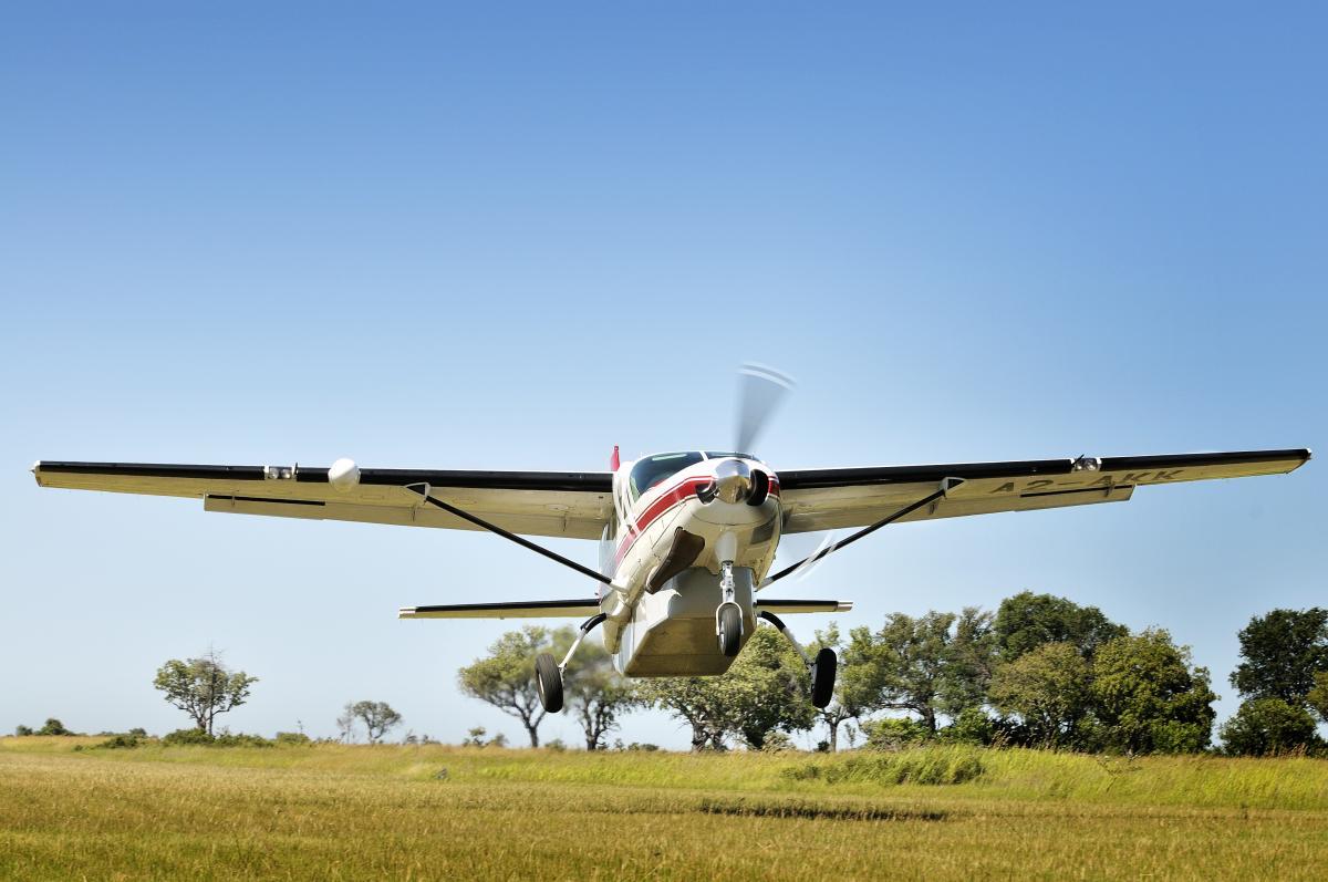 Flugzeug des Typs Propelormaschine hebt ab in die Flitterwochen vom Rollfeld in Afrika in der Savanne