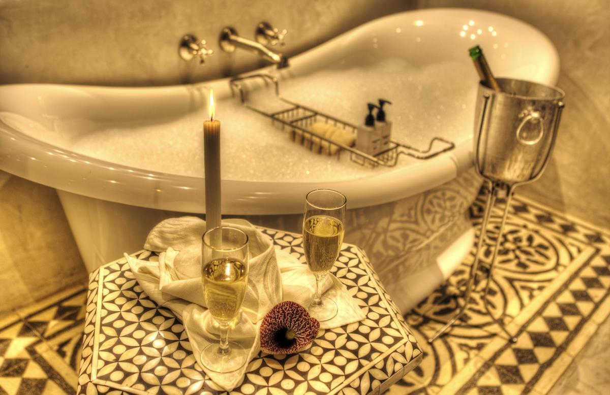 antike Badewanne mit Löwenfüssen, dazu Champagner-Flasche, Glässer und schönes Schaumbad zum Relaxen