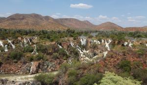 Die Ausläufe der Epupa Fälle in Namibia ziehen sich wie grüne Bänder durch die aride Landschaft des Kaokoveldes