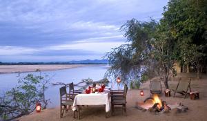 Nehmen Sie ein romantisches Dinner direkt am Luangwa Fluss im Island Bush Camp in Zambia ein