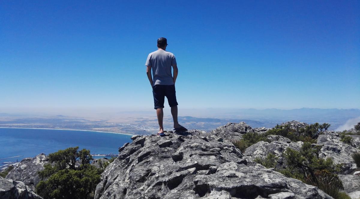 Mann steht am Rand des Plateau des Tafelberg in Südafrike und schaut über das Panorama von Kapstadt.