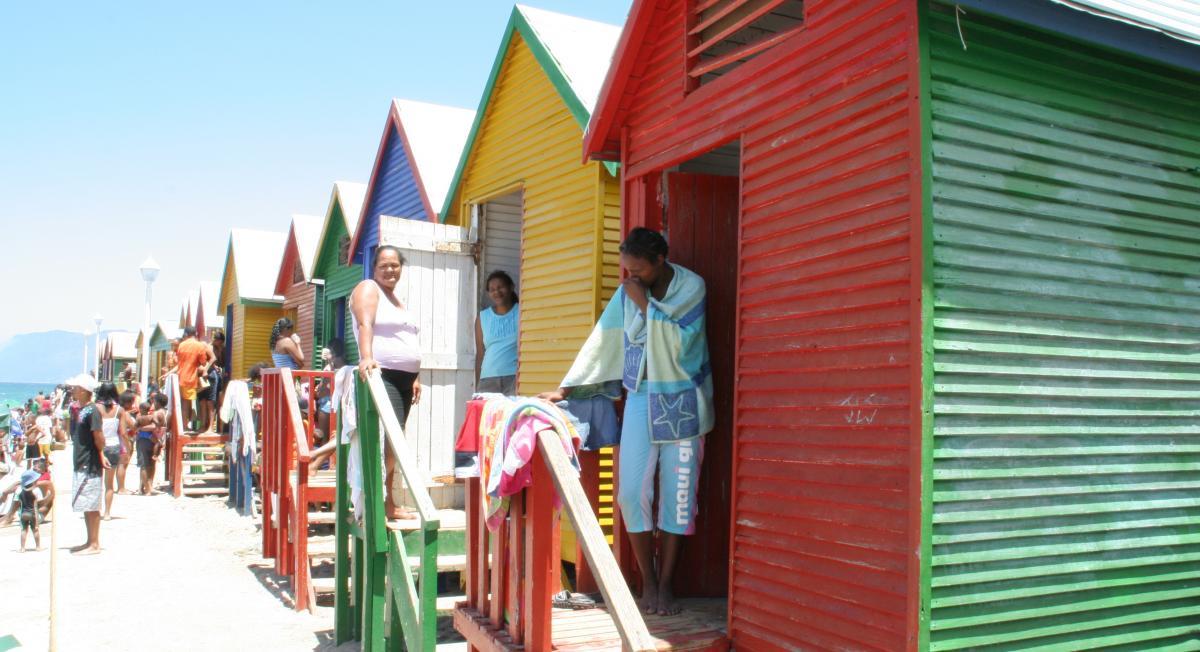 Bunte Strandhäuser, die als Umkleiden genutzt werden, badende Menschen und Badegäste sonnen sich. Weißer Sandstrand.