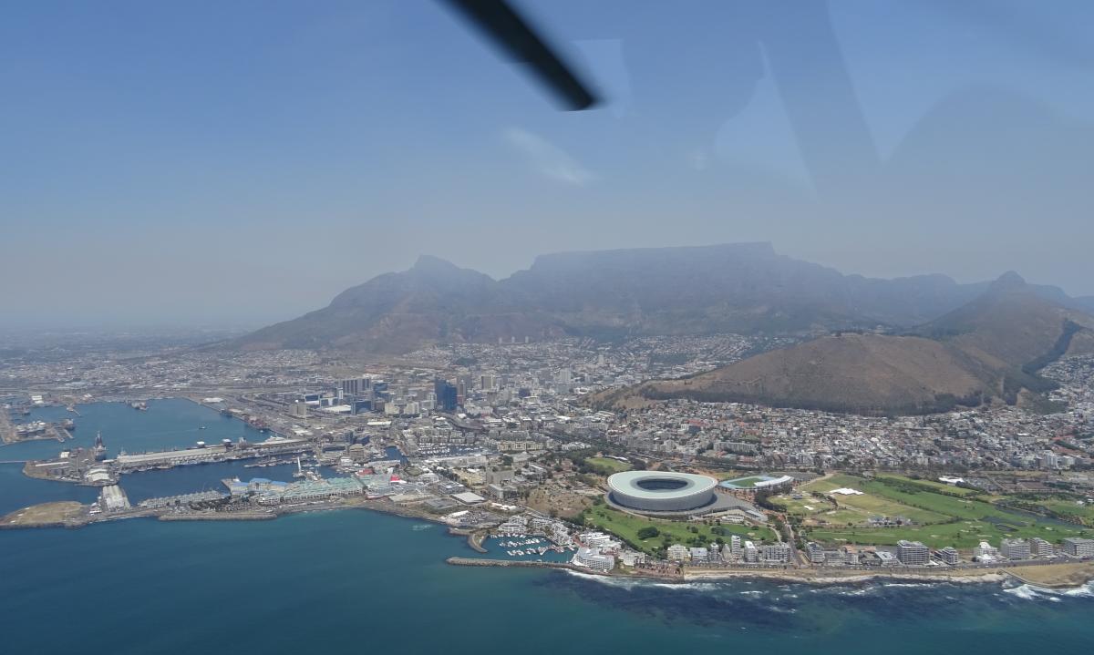 Blick aus dem Helikopter auf den tafelberg und die Innenstadt von Kapstadt. ein Rotorblatt des Heli zeigt sich im blauen Himmel. Das Ufer ist weiß von den Wellen eingerahmt.