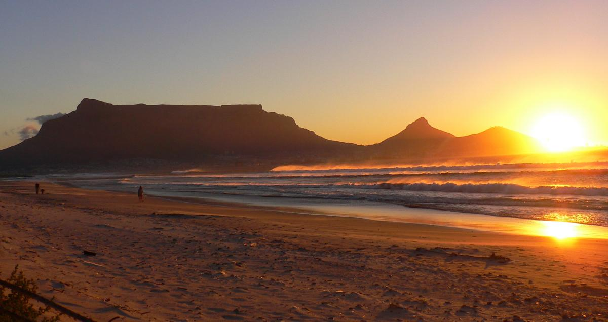Der Tafelberg aus der Ferne in Panoramaansicht zu sehen. Unter ihm liegt die Stadt Kapstadt mit ihrer Skyline am Meer. Davor spiegelt sich die Sonne im Meer und in den Wellen der Brandung am Strand.