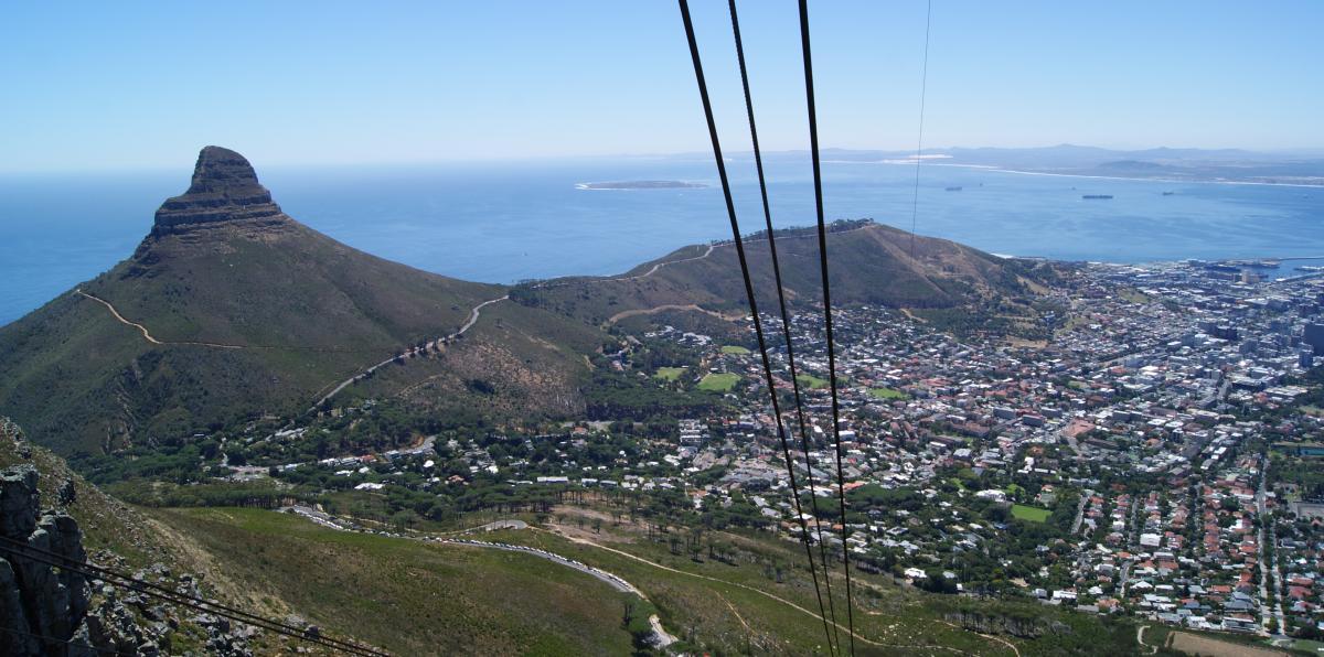 Aussicht und Panorama vom Tafelberg auf Kapstadt und die Tafelbucht. In der ferne ist Robben Island zu erkennen. Die sonne schein. Im Vordergrund verlaifen die seile der Seilbahn auf den tafelberg.