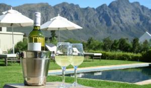 Entspannen Sie sich bei einem Glas Wein am Pool des La Cabrière Country House in Franschhoek