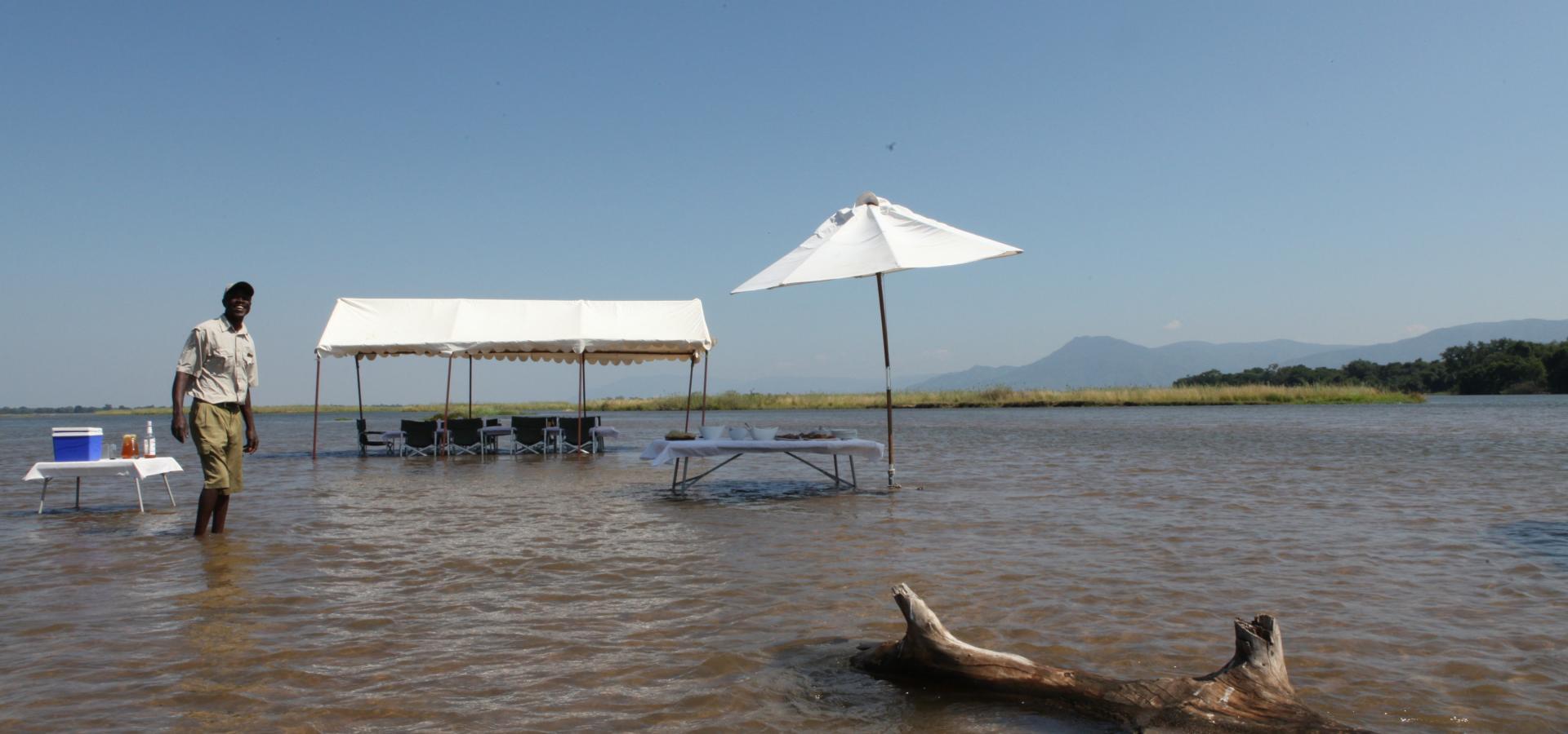 Nehmen Sie Ihr Lunch im seichten Wasser des Zambezi Flusses in einer einzigartigen Kulisse ein